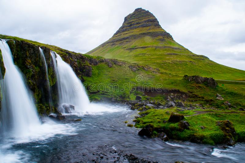 Kirkjufell volcano mountain, long exposure waterfall,  Iceland. Scenic panorama view of long exposure falling water in front of Kirkjufell volcano mountain, the stock photography