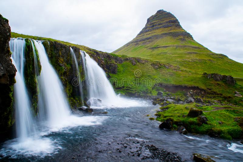 Kirkjufell volcano mountain, long exposure waterfall,  Iceland. Scenic panorama view of long exposure falling water in front of Kirkjufell volcano mountain, the royalty free stock image