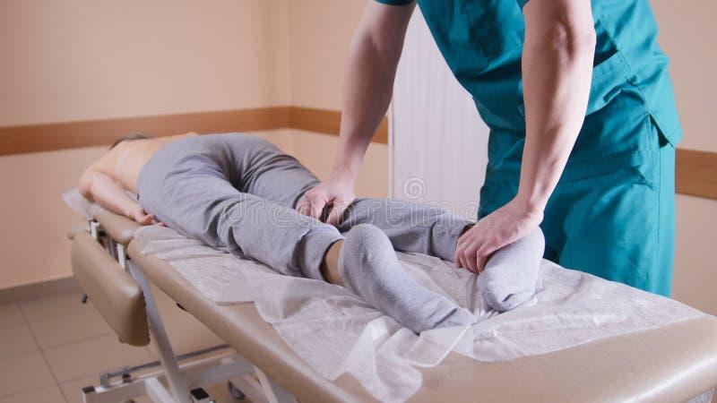 Kiropraktor som masserar en ung kvinna som ligger på en massagetabell, sträcker och böjer hennes fot och knä, närbild av fotografering för bildbyråer