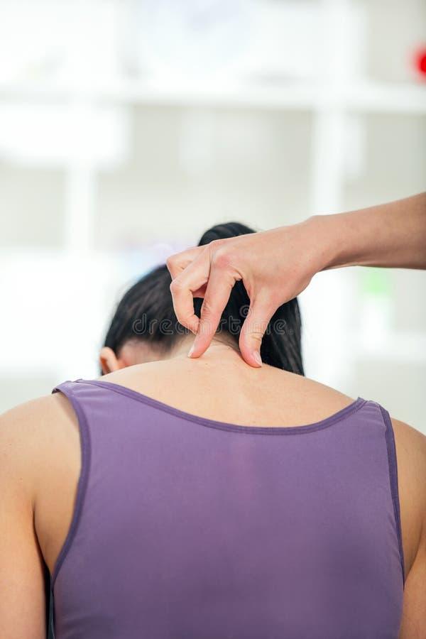 Kiropraktorn som justerar halsen, tränga sig in till kvinnlign royaltyfri bild