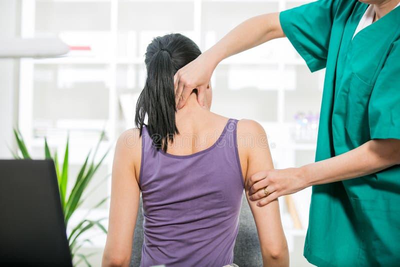 Kiropraktorn som justerar halsen, tränga sig in till kvinnlign arkivfoto