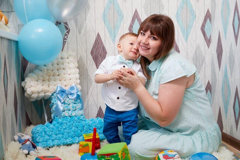 Kirov, Rússia - 10 de novembro de 2019: Criança masculina pequena com a mãe gorda no assoalho durante uma sessão fotográfica foto de stock royalty free