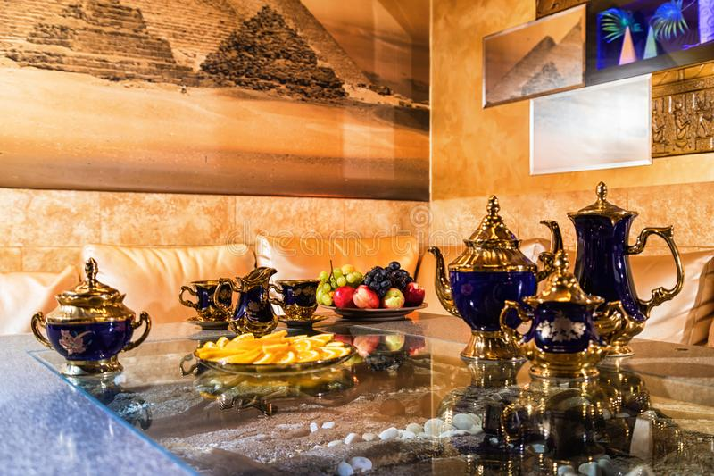 Kirov, Russia - July 18, 2018: Very beautiful and expensive porcelain tea set including cups, plates, kettle standing on a shiny. Black table stock photography