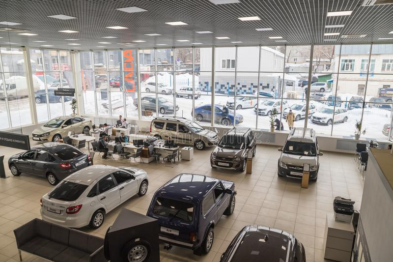 Cars, manager and customer in showroom of dealership AVTOVAZ named SeverAvto in Kirov city in 2018. Top view. Kirov, Russia - March 06, 2018: Cars, manager and royalty free stock image