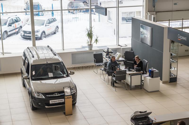 Cars, manager and customer in showroom of dealership AVTOVAZ named SeverAvto in Kirov city in 2018. Top view. Kirov, Russia - March 06, 2018: Cars, manager and stock photos