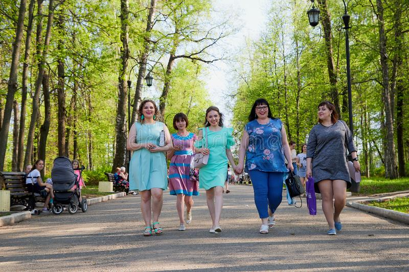 Kirov, Russia - May 11, 2019: Group of female friends walking in the park stock image