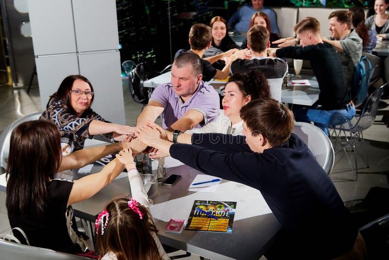 Kirov Ryssland - April 18, 2019: Folk på tabeller i kafét eller restaurangen som är glade något Intellektuell lek inomhus royaltyfria bilder