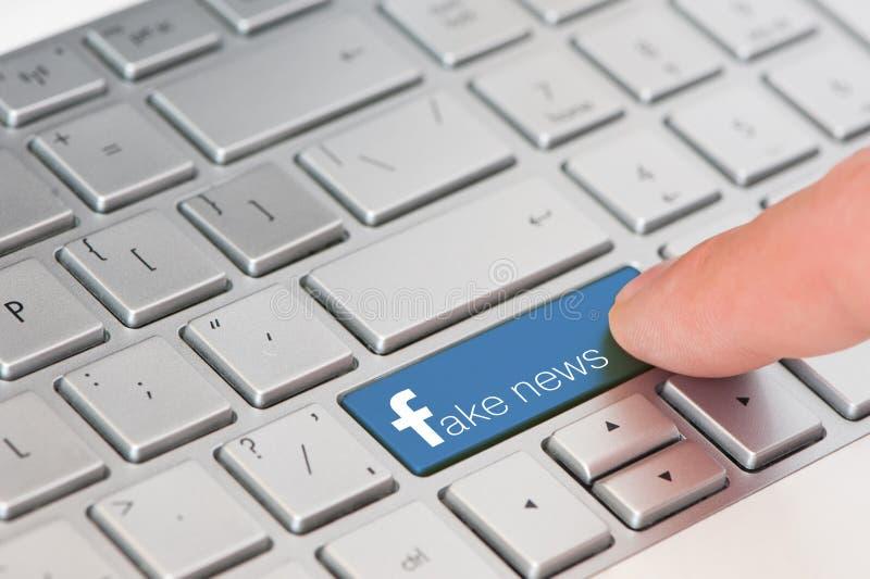 KIROVOGRAD UKRAINA, MARS, 12,2018 - tangenten med text fejkar nyheterna på det vita bärbar datortangentbordet Facebook stil arkivfoto