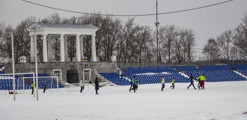 Kirovsk, Rússia, o 17 de março de 2019 Futebol do jogo de crianças no estádio na neve foto de stock