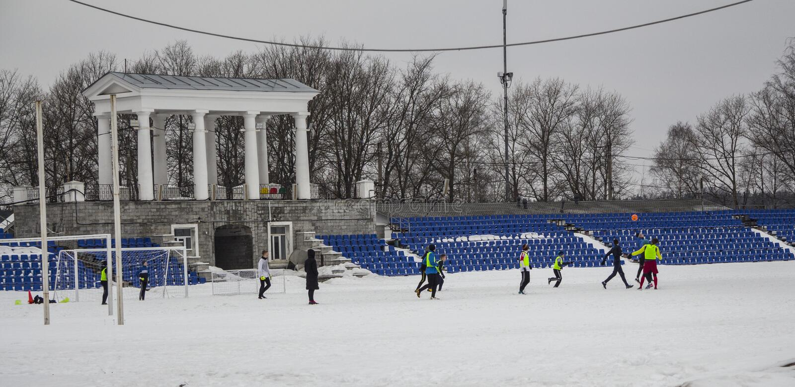 Kirovsk, Russia, March 17, 2019. Children play football in the stadium on the snow stock photo