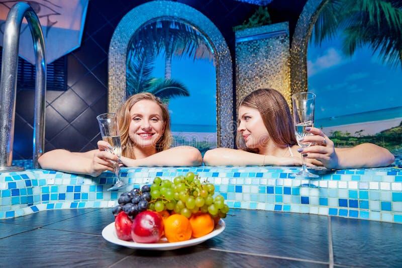 Kirow, Russland - 27. Februar 2019: Schönes Mädchen zwei mit dem langen Haar genießend im Swimmingpool und in einer Platte der Fr lizenzfreie stockbilder