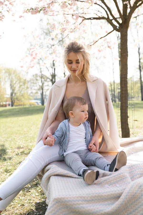 Kirschbl?te-Kirschbl?te - junge Muttermutter, die mit ihrem Babysohn des kleinen Jungen in einem Park in Riga, Lettland Europa si stockbilder