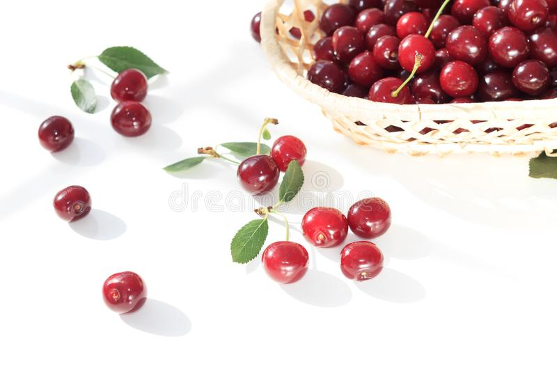 Kirsche der frischen Frucht im Weidenkorb auf weißem Hintergrund stockbilder