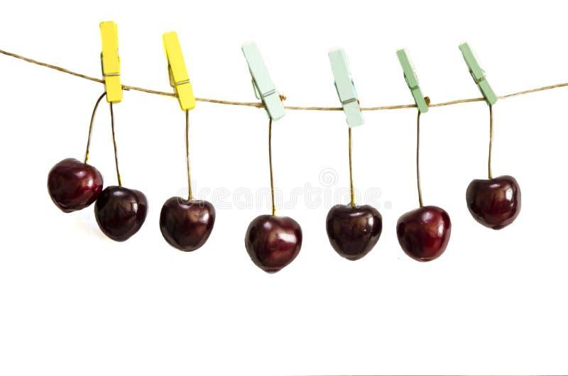 Kirsche, die an einer Wäscheklammer auf einem Seil hängt stockbild