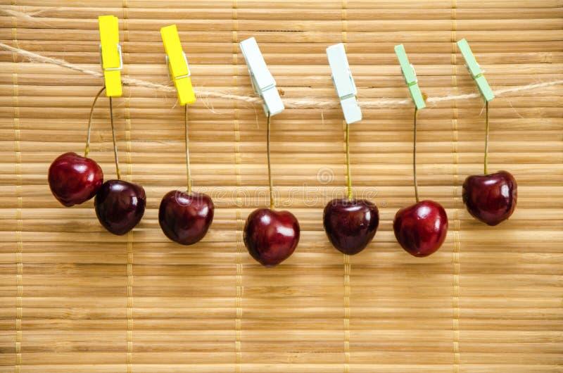 Kirsche, die an einer Wäscheklammer auf einem Seil hängt stockfoto