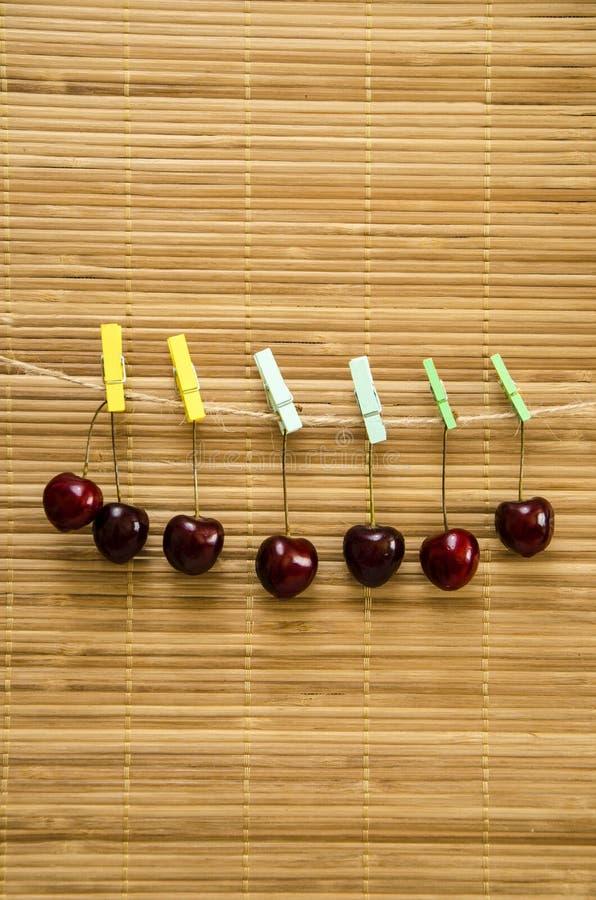 Kirsche, die an einer Wäscheklammer auf einem Seil hängt lizenzfreie stockfotos