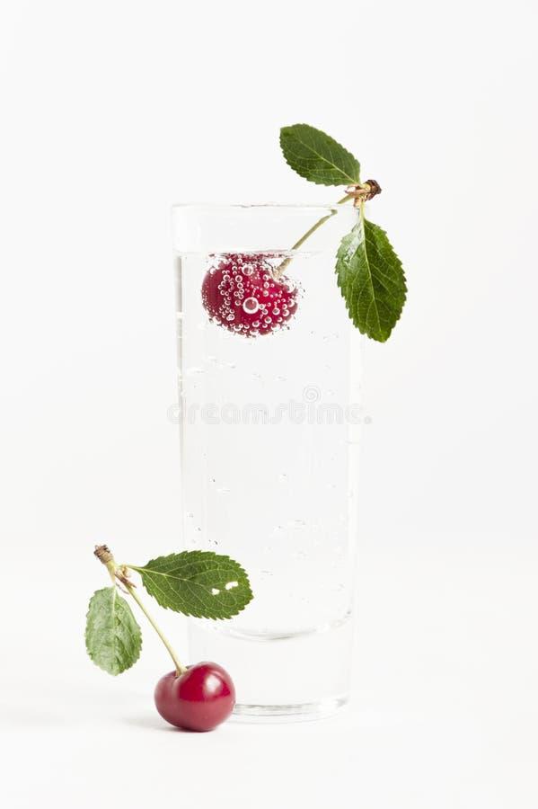 Kirsche mit Blasen im Glas des Wassers stockbilder