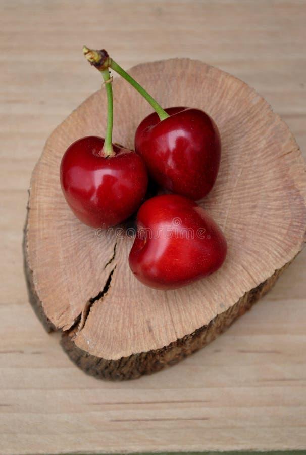 Kirschen auf einer Scheibe der Eiche lizenzfreies stockfoto