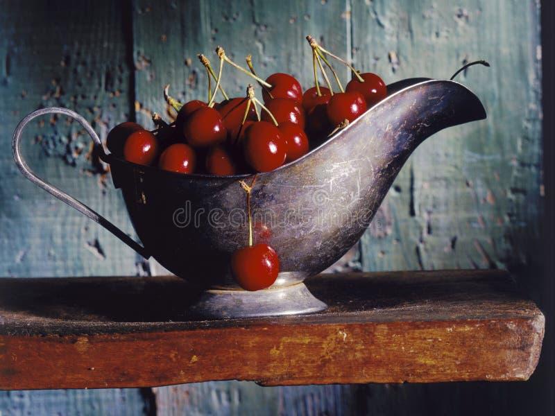 Kirschen in einem Soßeboot lizenzfreies stockfoto