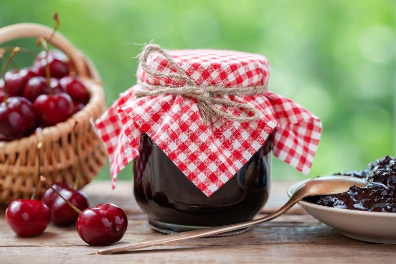 Kirschmarmelade, Kirschkorb, Saucer und Löffel auf dem Tisch lizenzfreies stockfoto