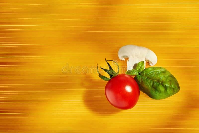Kirschtomate, -pilz und -basilikum auf rohem Spaghettiteigwaren backgro lizenzfreie stockfotografie