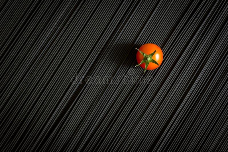 Kirschtomate und rohe schwarze Teigwaren lizenzfreie stockfotos