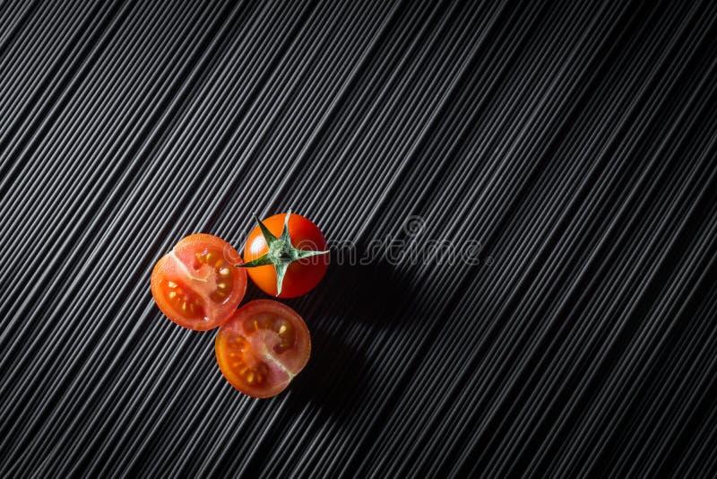 Kirschtomate und rohe schwarze Teigwaren stockbild