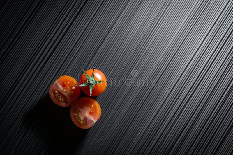 Kirschtomate und rohe schwarze Teigwaren stockfoto