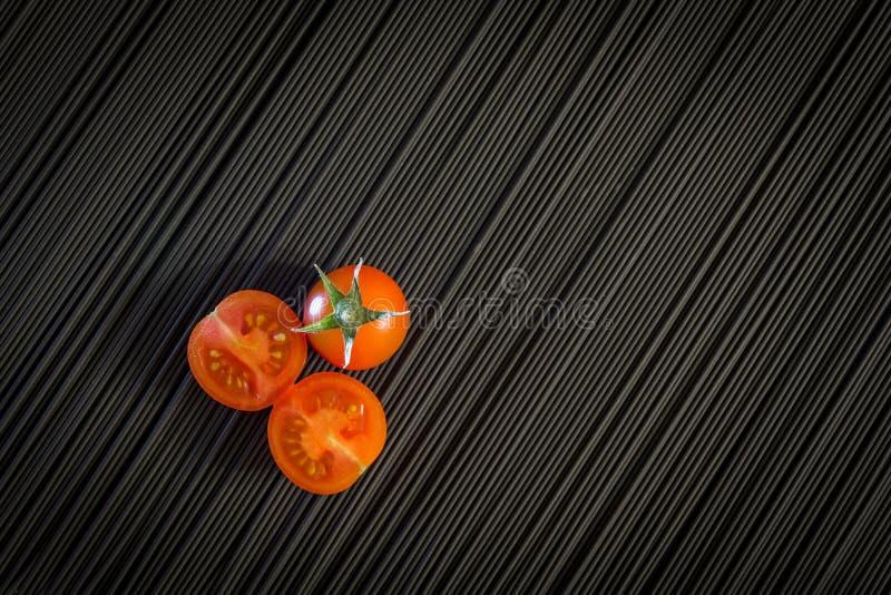 Kirschtomate und rohe schwarze Teigwaren stockfotografie
