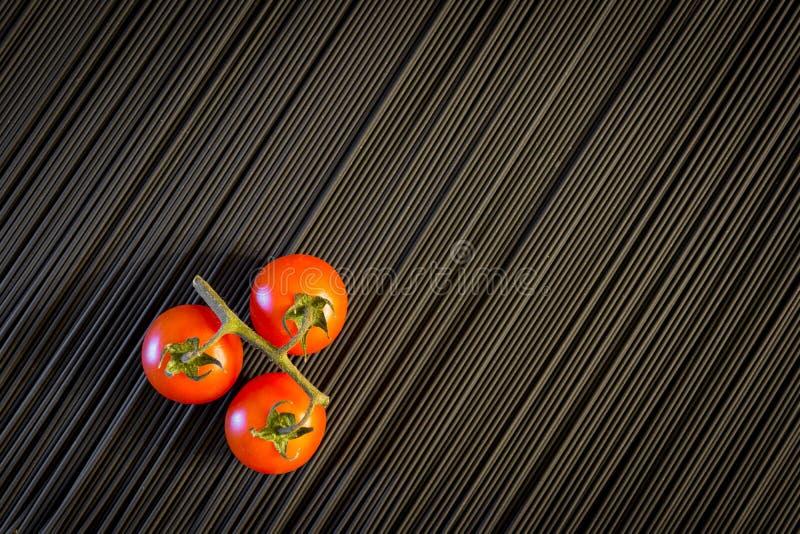 Kirschtomate und rohe schwarze Teigwaren stockfotos