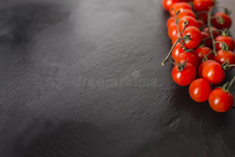 Kirschtomaten über einer schwarzen Steinplatte mit Kopienraum stockfotos