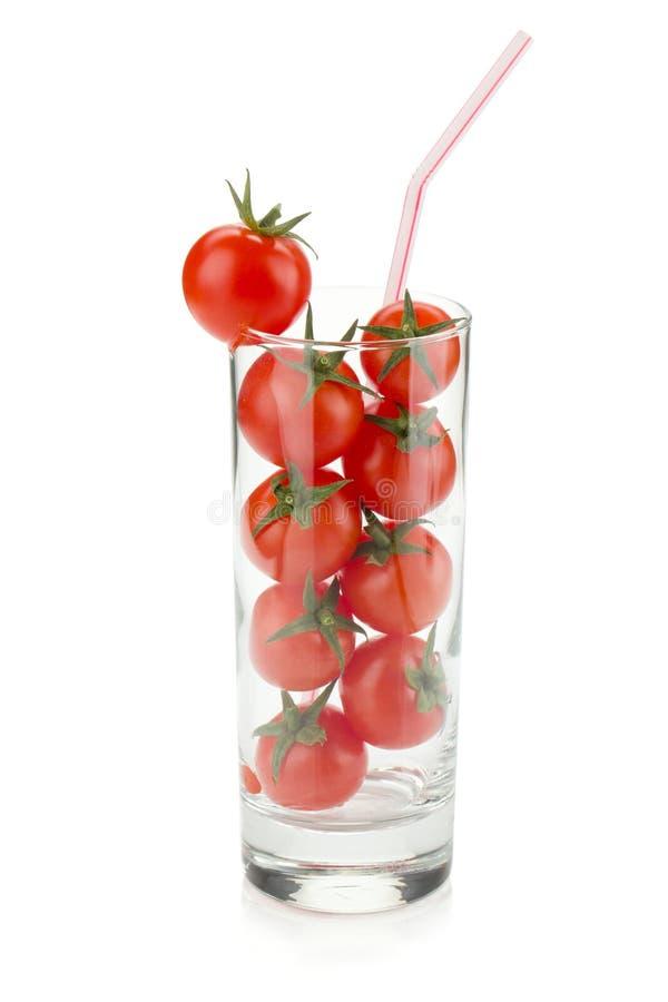 Kirschtomaten im Glas mit Trinkhalm lizenzfreie stockfotos