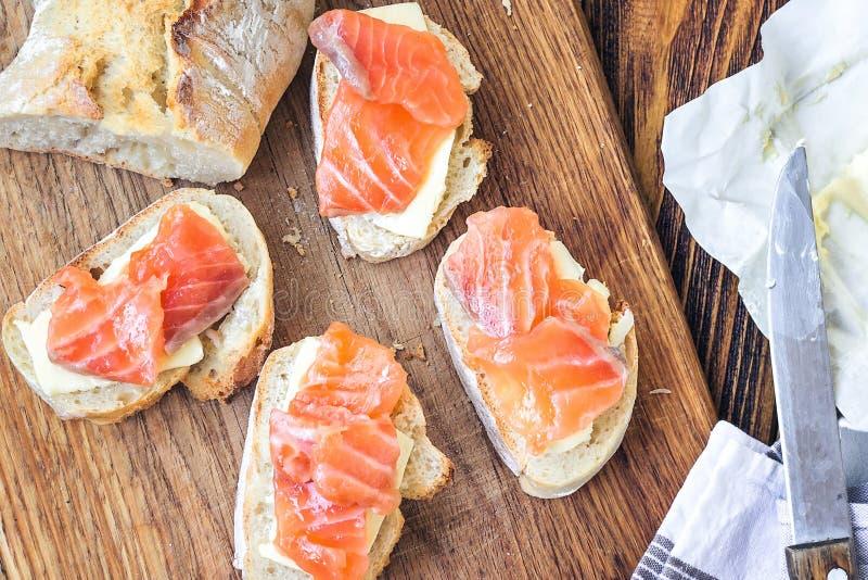 Kirschtomaten mit Mozzarella Aperitif Canapessandwiche mit Stangenbrot, Lachsen und Butter auf rustikalem hölzernem Brett über hö stockbild