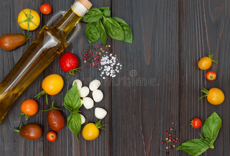 Kirschtomaten, Mozzarella, Basilikumblätter, Gewürze und Olivenöl von oben Italienische caprese Salatrezeptbestandteile lizenzfreie stockbilder