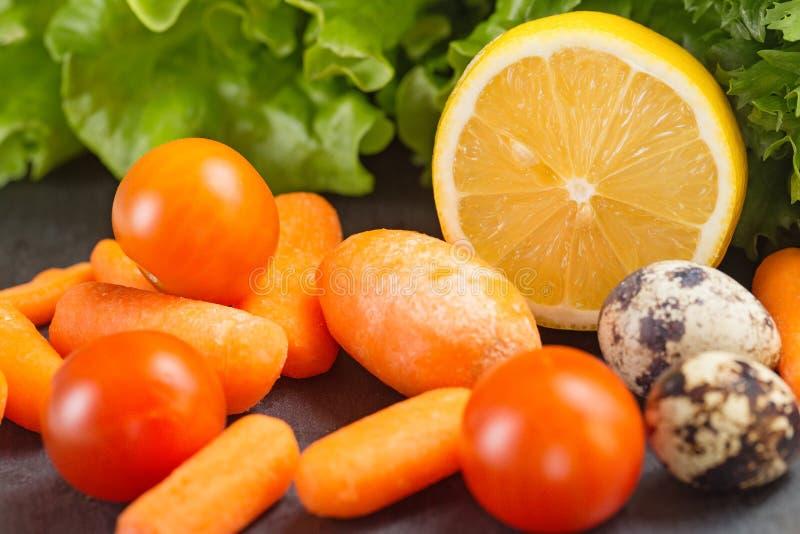 Kirschtomaten, Salatblätter, Zitrone, Karotten und Wachteleier schließen oben stockfotos