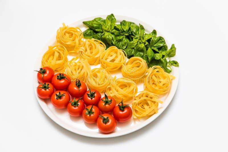 Kirschtomaten, Spaghettis und frischer Basilikum auf einer Servierplatte auf einem weißen Hintergrund stockbilder