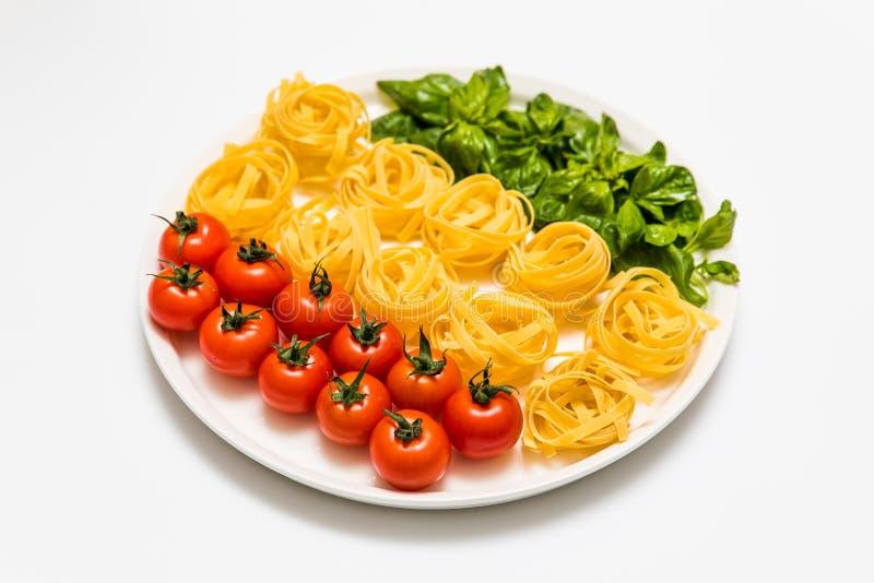 Kirschtomaten, Spaghettis und frischer Basilikum auf einer Servierplatte auf einem weißen Hintergrund lizenzfreies stockbild