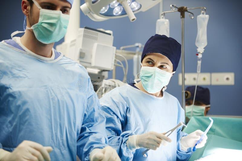 Kirurger som tillsammans arbetar stundoperation royaltyfria foton