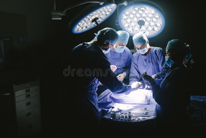 Kirurger som utför kirurgiskt tillvägagångssätt i operationssal royaltyfria foton