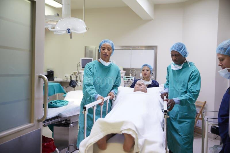 Kirurgiska Team Wheeling Senior Male Patient ut ur sjukhusoperationssal royaltyfri foto