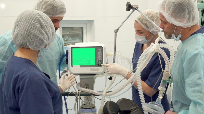 Kirurgiskt lag som diskuterar något på bildskärm royaltyfria foton