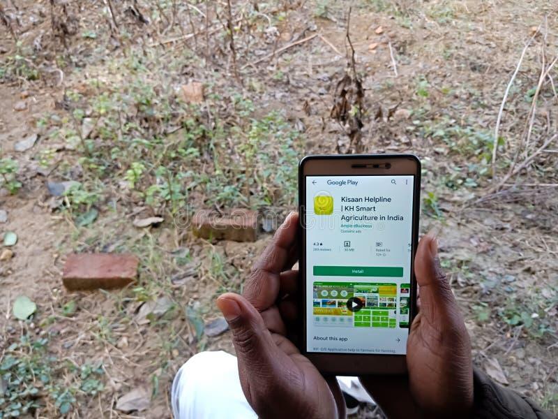 Kisaan-Helpline-Bauern unterstützen Anwendungssoftware, die auf dem Handy auf dem Landwirtschaftsfeld in Indien im Dezember 2019  lizenzfreies stockfoto