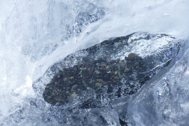 Kiselstenstenar inneslutade i ett smältande iskvarter på diamantstranden, Island royaltyfri foto