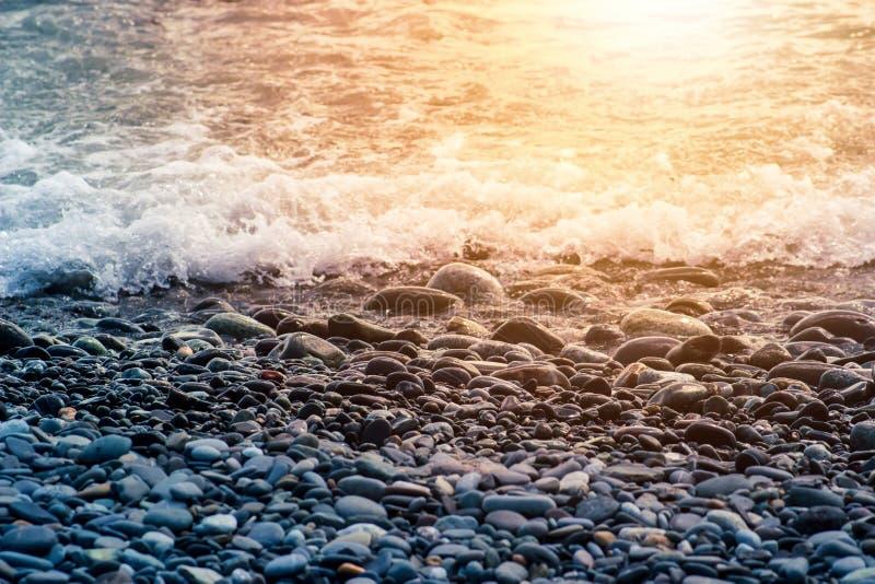 Kiselstenstenar p? kustslutet upp i det oskarpa solnedg?ngljuset i avst?ndsbakgrunden royaltyfri foto