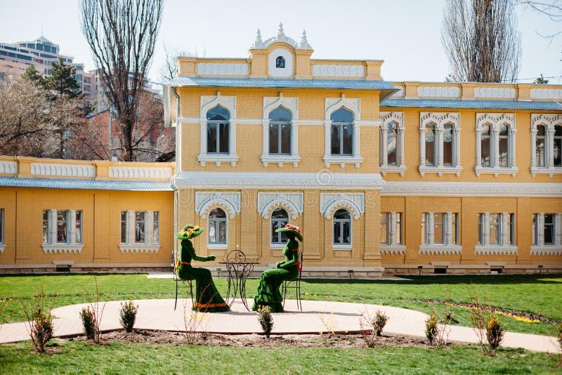 Kislovodsk, región de Stavropolsky, Rusia - 10 de abril de 2018: esculturas verdes bajo la forma de mujeres que beben té en fotografía de archivo libre de regalías