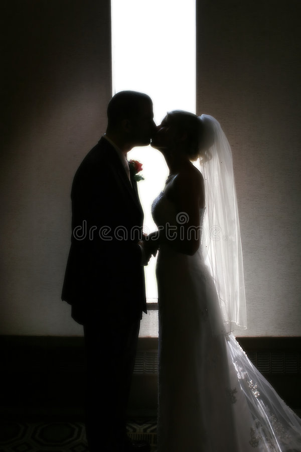 Kiss. A silhouette of a bride and groom kissing in front of a narrow window
