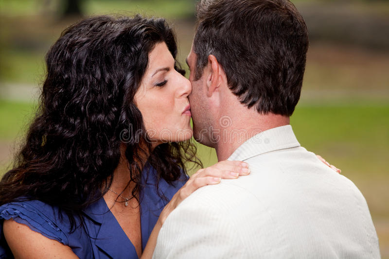 Kiss. A woman giving a man a kiss on the cheek stock images