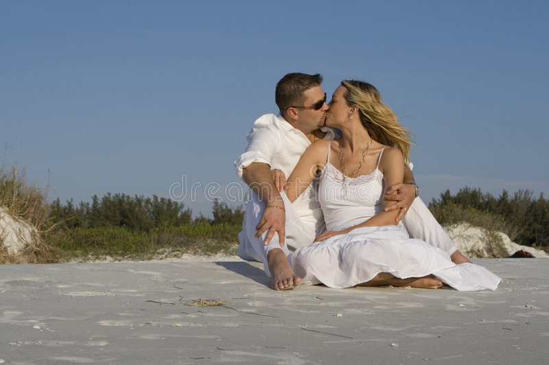Kiss. Man and a woman sitting on a beach, kissing. Both wearing white clothes stock photography