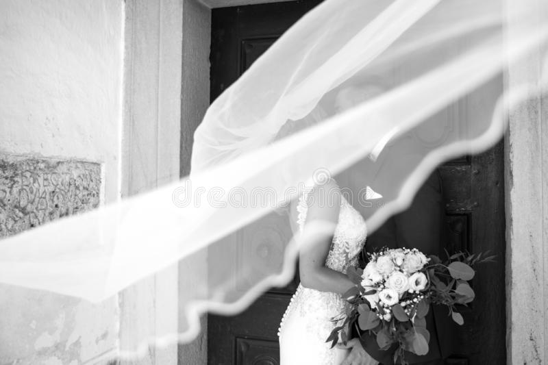 The kiss. Bride and groom kisses tenderly in the shadow of a flying veil. Artistic black and white wedding photo. royalty free stock photo