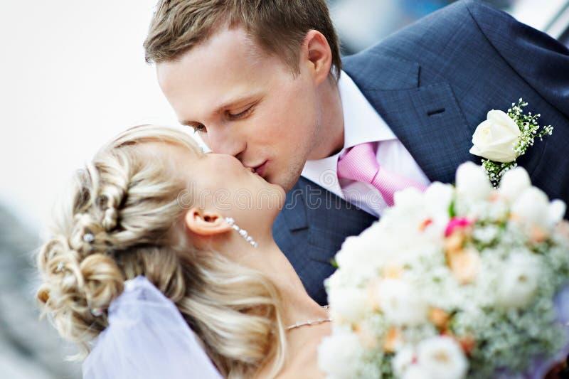 Kiss bride and groom at wedding stock image